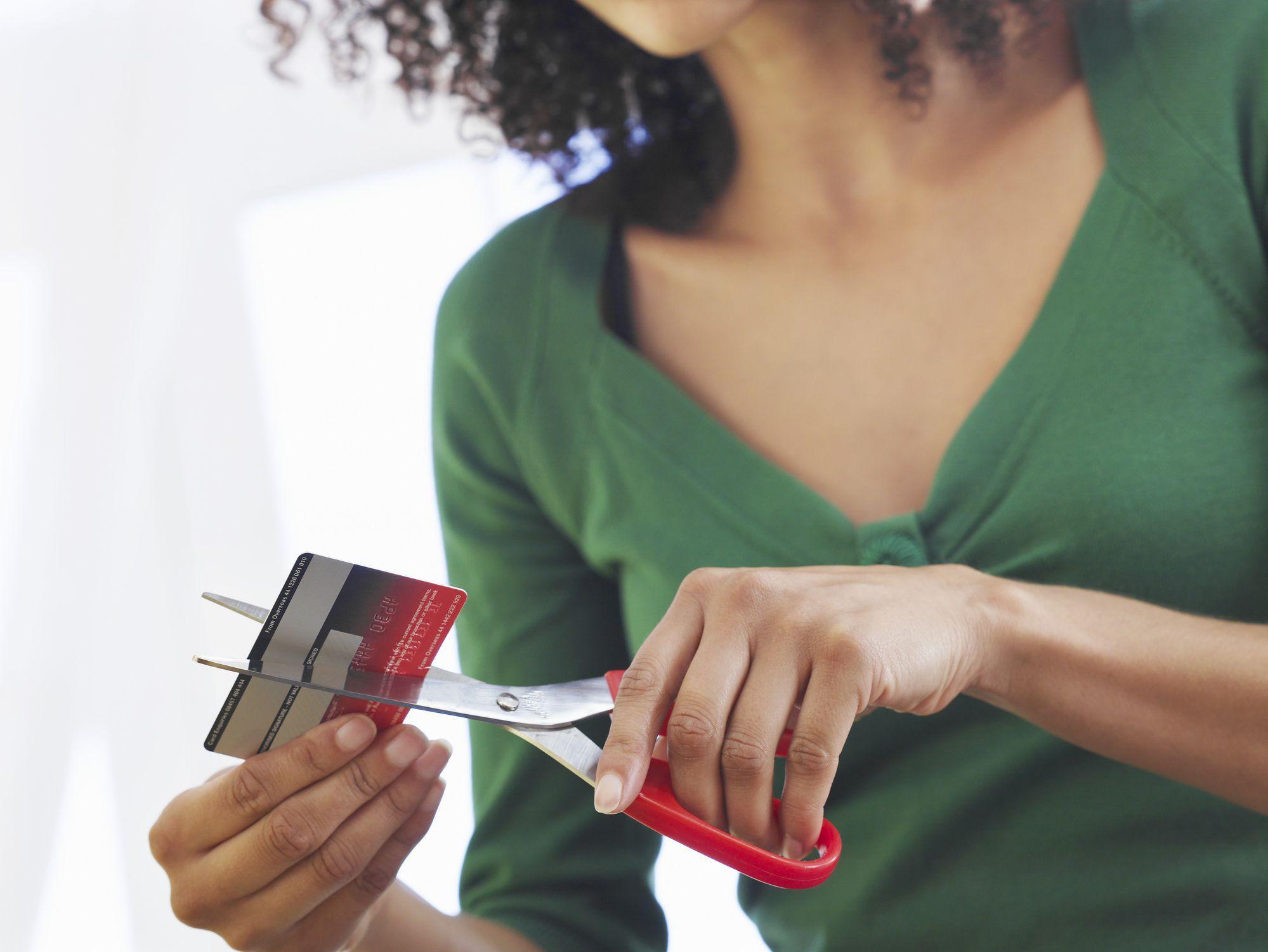padrão de vida: mulher cortando cartão de crédito